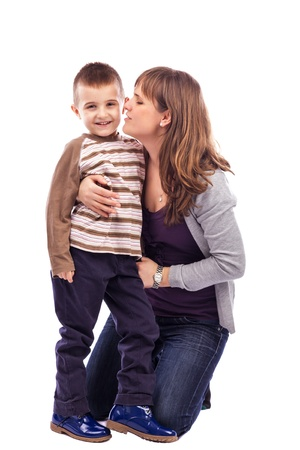 Portrait of a young mother kissing her smiling little boy over white background