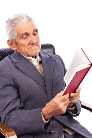 Portrait of an old man reading a book sitting in his armchair  isolated on white background photo