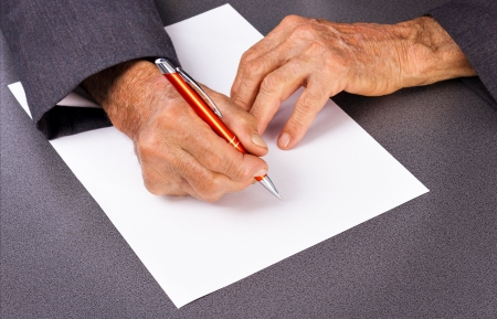 Old man´s hands writing with a pen on a sheet of paper Stock Photo