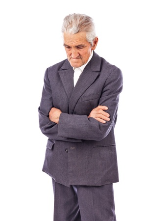 lost in thought: Elderly man with arms folded looking down lost in deep thought on white background