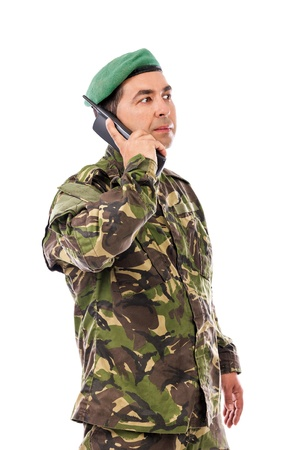 Young army soldier with beret speaking on phone isolated on white background photo