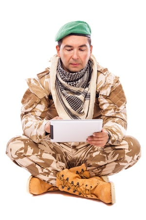 Young soldier using his tablet computer against a white background photo
