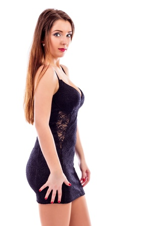 Beautiful young woman with long  brown hair wearing short black dress isolated on white background