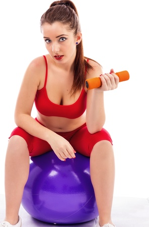 Young pretty woman lifting up dumbbells while sitting on a gym ball isolated on white background photo