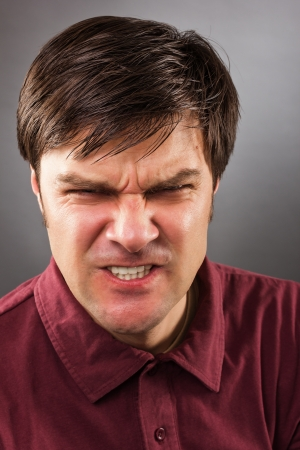 Closeup portrait of an angry man against gray background