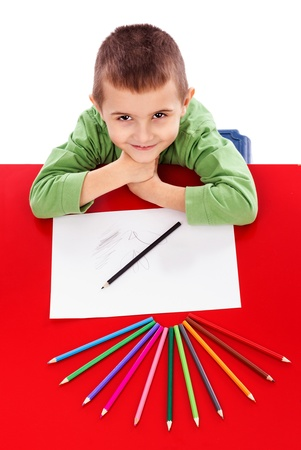 Happy little boy at the table drawing with crayons and looking up isolated on white Stock Photo - 19669058