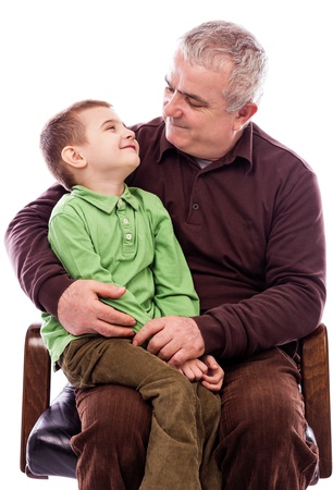 Portrait of a grandpa with his happy grandson sitting in armchair isolated on white background photo