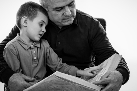 Portrait of a  man reading a story book for his grandson over white.Monochrome portrait photo