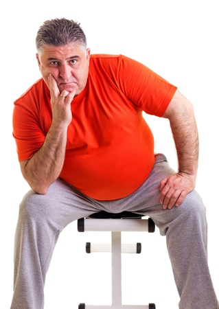 Overweight man sitting on a bench for abdominals, he takes a break, isolated on white background