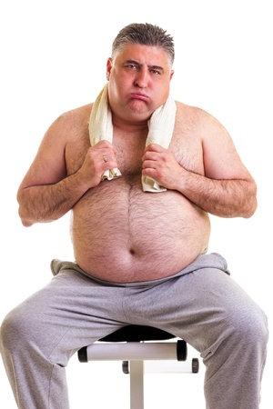 Overweight man resting on a bench for abdominals, tired after training, over white background