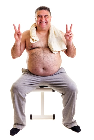 Overweight man resting on a bench for abdominals and showing victory sign on white background photo
