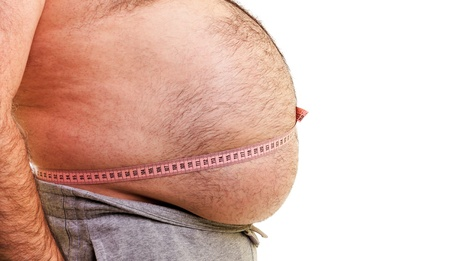 Closeup of a big belly surrounded by a measuring tape over white background photo