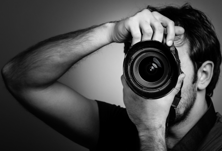 Young man with professional camera. Monochrome portrait Stock Photo