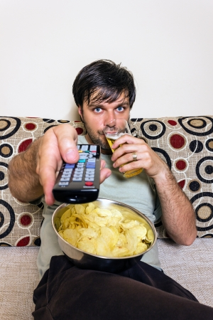 man couch: Young man watching television, eating potato chips and drinking beer indoor