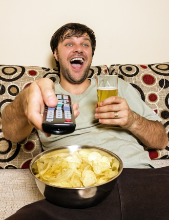Happy young man watching television, eating potato chips and drinking beer inside Stock Photo