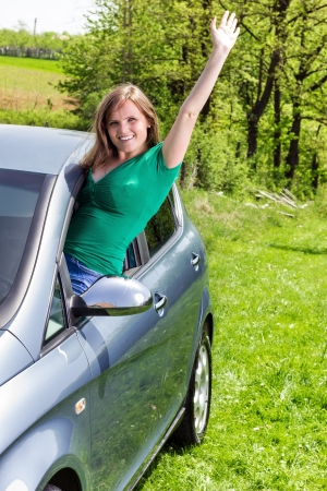 Happy young woman waving out the window of her new car  photo