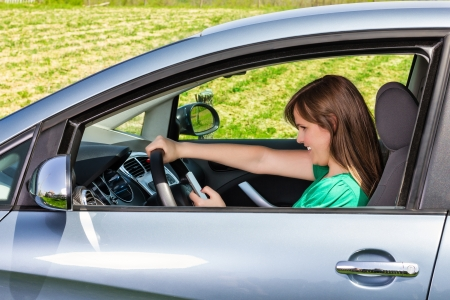 Smiling young woman driver readingtyping a text message on her mobil phone photo