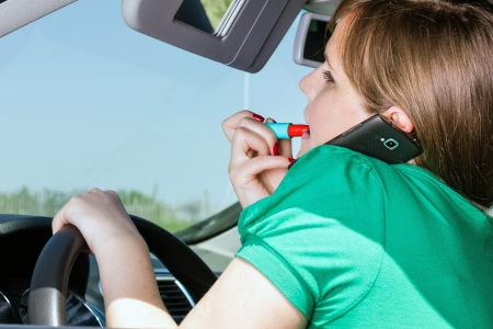 Young woman driving , applying lipstick and speaking on her smart phone in her car Stock Photo