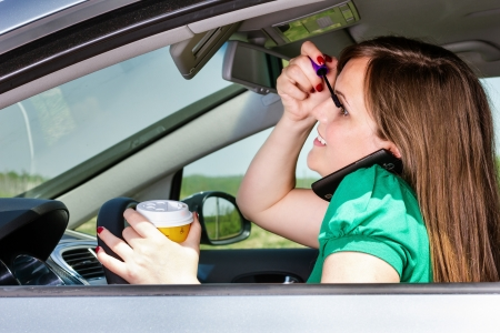 Pretty young woman applying makeup, speaking on phone and drinking coffee while driving her car