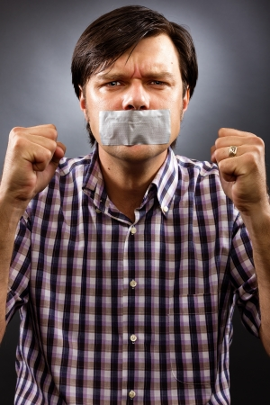 Angry  young man with duct tape over his mouth against gray background. Conceptual image photo