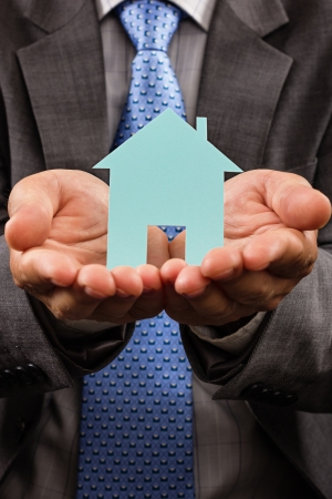 Business man holding a model of a house in his hands. Conceptual image