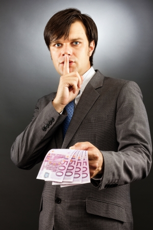 Young  businessman making silence gesture and holding euro banknotes  over gray background