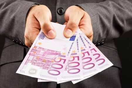 Businessman showing euro banknotes.Closeup Stock Photo