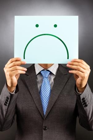 cara triste: Hombre de negocios con una cara triste aislado sobre fondo gris. Concepto