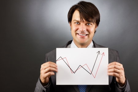 Businessman showing a rising graph, representing business growth on gray photo