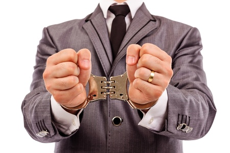 swindle:  Businessmans hands with handcuffs. Closeup