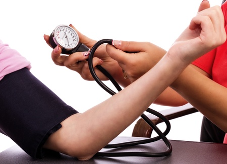 Doctor taking young woman blood pressure against white background photo
