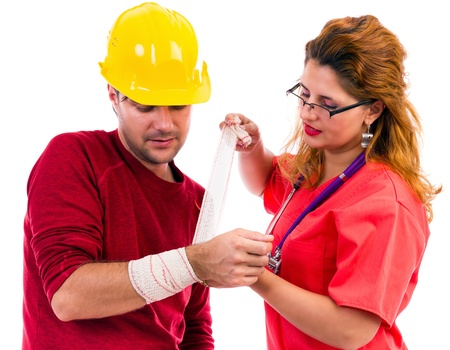 Female doctor/ nurse putting a bandage to a  construction worker on white