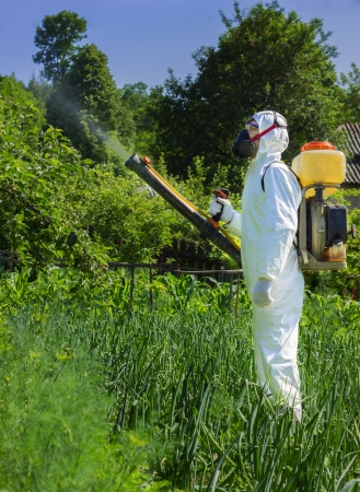 country farmer spraying insecticide in his garden