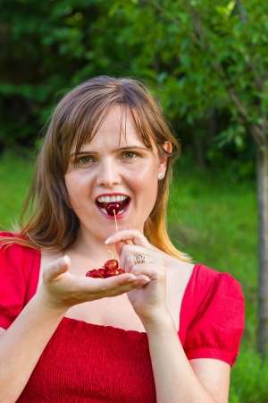 Young pretty blonde woman eating cherries  in garden at summer photo