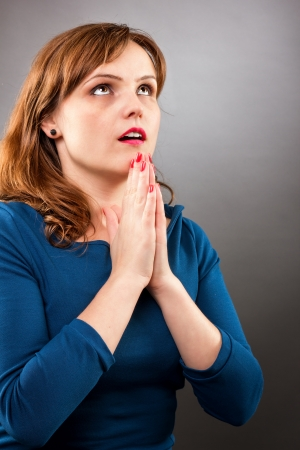 Closeup portrait of a young woman praying while looking up on white background photo