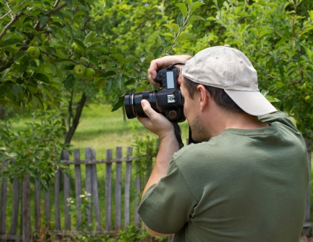 photographer taking a photo in an apple garden photo
