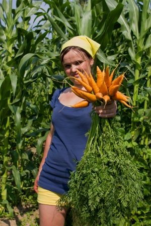 young woman with a bunch of carrots in nature photo