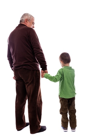 Senior man holding his grandsons hand, back view, isolated on white background