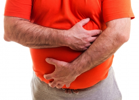 Man holding both hands on his aching stomach, closeup, over white background photo