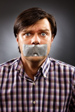 Young man with duct tape over his mouth against gray background. Conceptual image photo