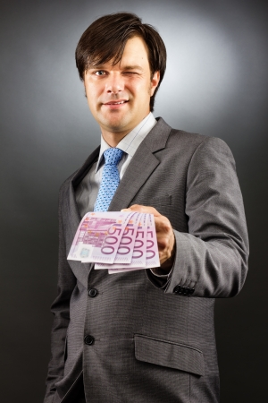 Young  businessman winking and showing euro banknotes over gray background photo