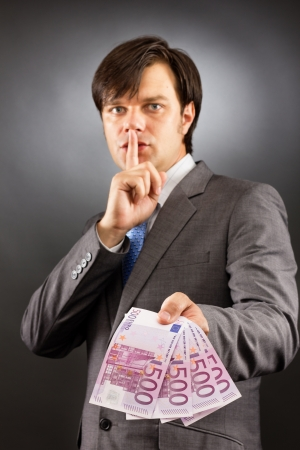 Young  businessman making silence gesture and holding euro banknotes  over gray background photo