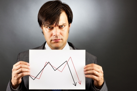 empresario enojado: Angry hombre de negocios que muestra un gr�fico de la ca�da del mercado de valores en contra de gris