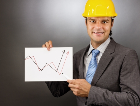 Young engineer drawing a rising graph, representing business growth on gray photo