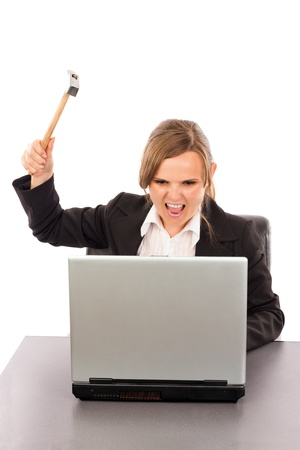 Angry businesswoman with a hammer ready to smash her laptop while sitting at office desk isolated on white photo