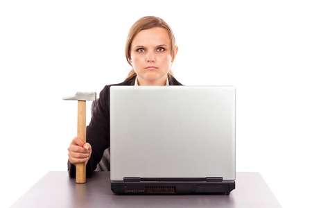 Serious businesswoman with a hammer sitting at office desk isolated on white photo