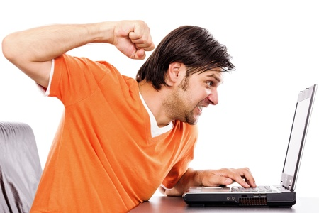 Angry young man at laptop isolated on white