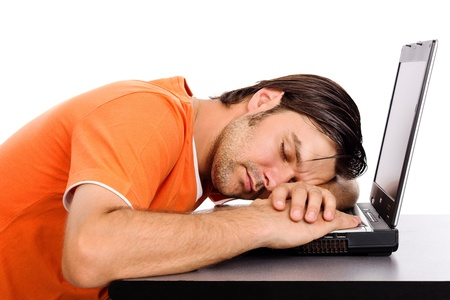 somnolence: Young man taking a nap on his laptop isolated on white background Stock Photo