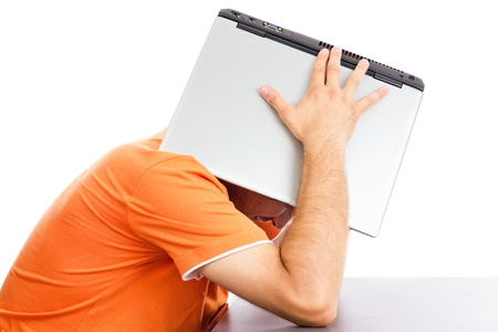 Exhausted young man covering his head with his laptop against white background Stock Photo