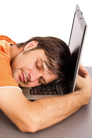 in somnolence: Young man taking a nap on his laptop isolated on white background Stock Photo